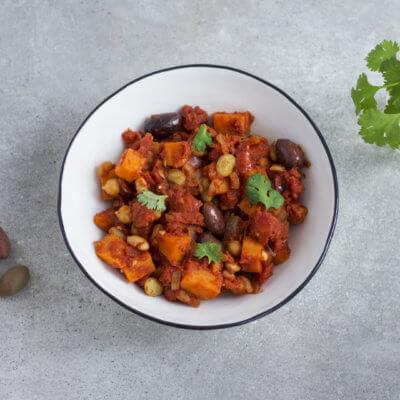 Marokańskie danie z jednej patelni z pomidorami, oliwkami, ciecierzycą, fasolą i batatem