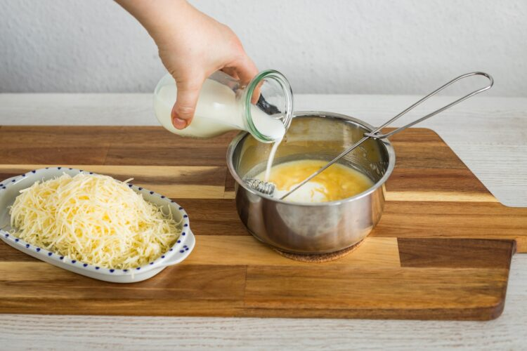Jajka zapiekane z szynką, pomidorkami i kukurydzą w sosie serowym - Krok 2